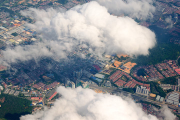Aerial view of the modern city in Malaysia with houses, streets. Vew from an airplane thru the clouds.