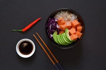Traditional Hawaiian dish Poke Bowl on a dark background ( salmon, avocado, rice, seawood, carrot, tomatoes)
