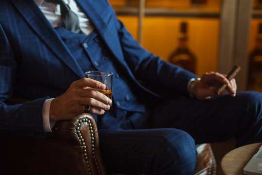 Well-dressed unrecognizable caucasian man in expensive tailored suit relaxing with cigar and alcohol, sitting at his office in leather chair