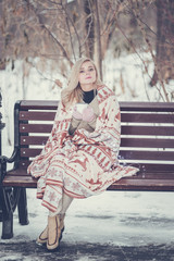 Pensive relax and happy girl with a warming drink sitting in the winter forest