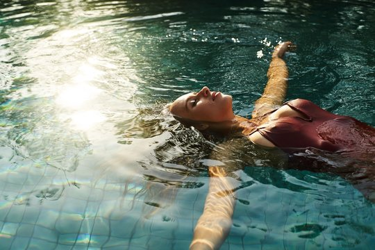 beautiful female relaxing in an outdoors swimming pool with sun reflactions on water surface