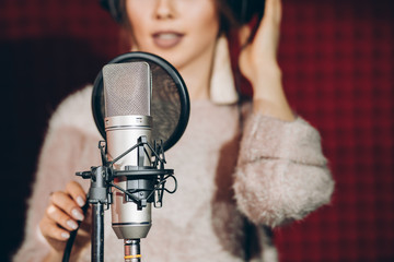 close up photo. talented female near the microphone. blurred background. tool, instrument, device