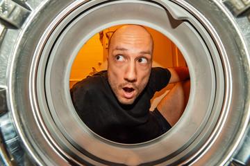 Portrait of man view from washing machine inside. What is that thing inside the washing machine?