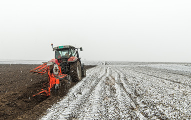 Tractor plowing a field Wall mural