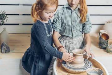 adorable kids is in the workshop of making pots. close up cropped shot