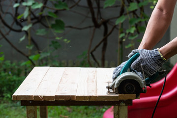 DIY sawing wood in the garden using handheld electrical saw