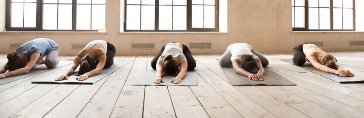 Five girls during yoga session at sport studio. Sportive females lying in row relaxing on wooden floor rubber mats doing Child Pose. Horizontal photography banner for website header. Wellness concept Wall mural