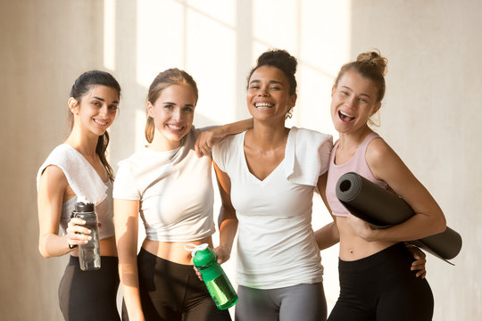 Indian biracial and caucasian beautiful women standing together smiling looking at camera girls drinking water after power training or yoga session feels happy and satisfied. Healthy lifestyle concept