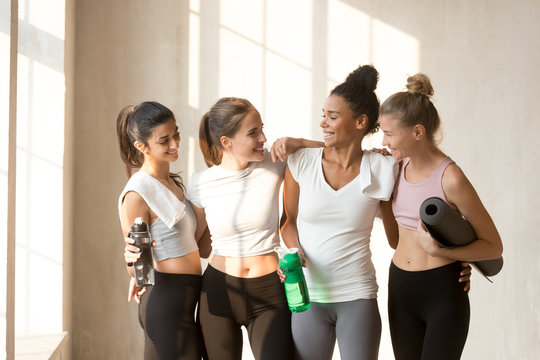 Diverse multi-ethnic slim women friends talking after workout resting standing in yoga class. Attractive girls looks perfect and healthy feels happy and satisfied after intense training in sport club