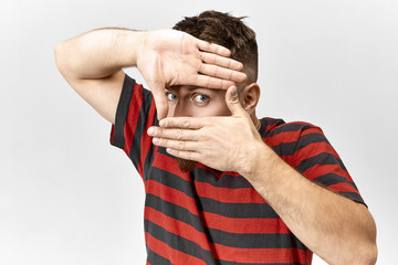 Funny stylish young man wearing red and black striped t-shirt posing indoors with hands at his face forming rectangular frame with only eye being seen, staring at camera as if taking picture