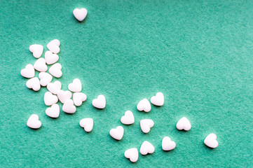Small white hearts on a green background. Greeting card for Valentine's Day. Copy space