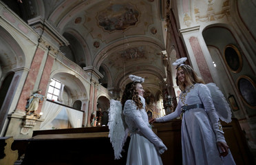 Women dressed as angels stand inside a church during a Christmas market in the town of Ustek