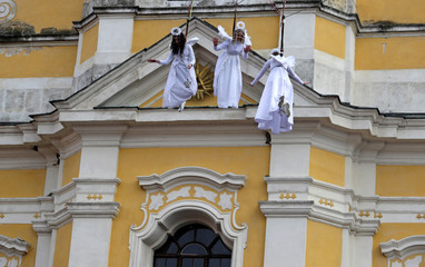 Women dressed as angels wave to spectators as they hang from a wire during a Christmas market in the town of Ustek