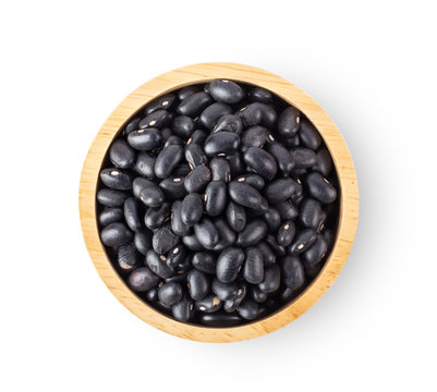 black beans in wood bowl isolated on white background. top view