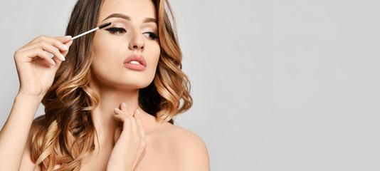 Beauty woman hold black mascara eyelashes  makeup brush clear healthy face portrait