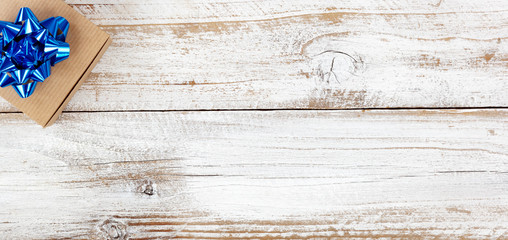 Gift box in left upper corner for the holiday seasons on white rustic wood with plenty of copy space