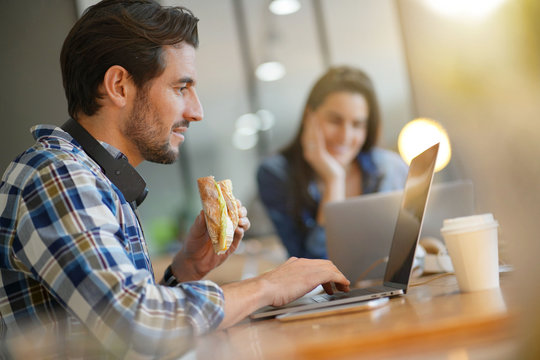 Attractive man eating sandwich whilst working in co working space