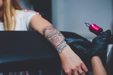 girl tattoo artist doing a tattoo on her hand, pink typewriter, on a black table.