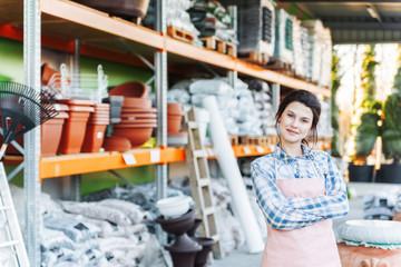 Woman gardener standing in storage of gardening supplies