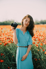 Beautiful girl with photo camera standing in poppy meadow.