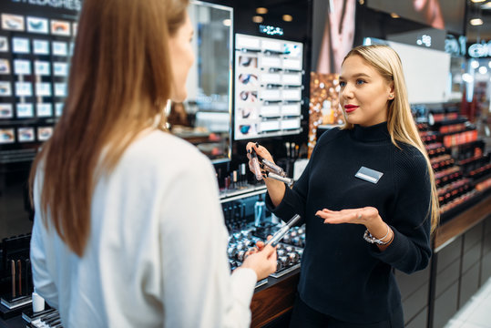 Seller shows to client eyeshadows in make-up shop