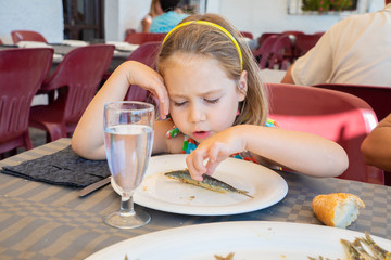 portrait of five years old blonde little girl with diadem eating a sardine cooked fish cooked in a white dish, sitting in restaurant on Summer