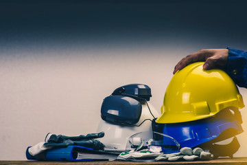 Works safety concept: PPE (Personal Protective Equipment), hard hat or industrial helmet for protection the worker from accident during working at construction site, factory or industry building.