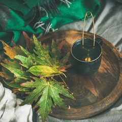 Mug of tea with fallen leaves on tray, square crop