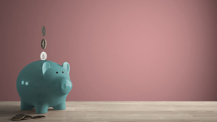 Wooden table top or shelf with turquoise piggy bank with coins, saving money for future investments, concept idea with pink colored background template with copy space Wall mural