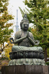 Bodhisattva Kannon statue with the Tokyo Skytree in the background at Sensō-ji, Tokyo's oldest Buddhist temple