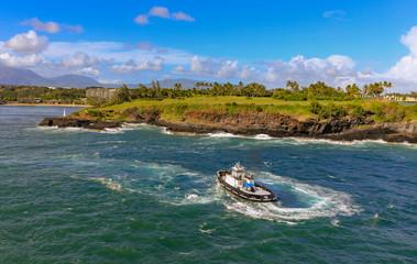 tug boat in the sea heading towards tropical island