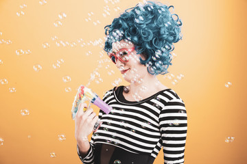 Cute girl wearing vibrant blue wig playing and blowing bubbles