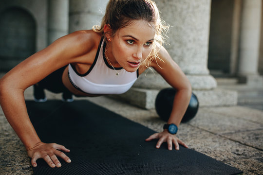 Fitness woman doing push ups on a yoga mat