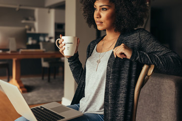 Thoughtful female having coffee while working on laptop at home