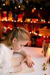 Blonde child girl writing letter to the Santa Claus or drawing something on the background with warm yellow bokeh. Christmas and New Year theme