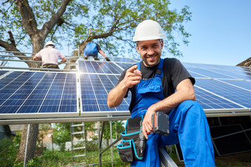 Portrait of smiling technician with electrical screwdriver pointing to camera in front of unfinished high exterior solar panel photo voltaic system with team of workers on high platform.