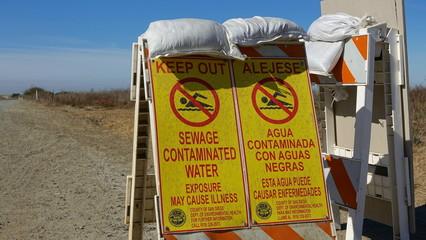 Signs  warn of sewage contaminated water near border
