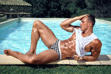 Muscular young sexy wet man in swimming underwear and white shirt is lying near the pool outdoors