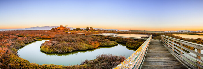 Wooden boardwalk through the tidal marshes of Alviso, Don Edwards San Francisco Bay National Wildlife Refuge, San Jose, California; sunset view Fototapete