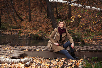 Happy young fashion woman sitting on wooden bridge in autumn park