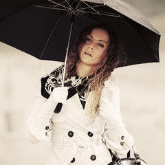 Beautiful fashion woman in white trench coat with umbrella