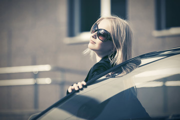 Happy young fashion woman in sunglasses leaning on her car
