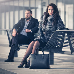 Young fashion couple in conflict sitting on bench
