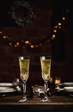 Christmas, New Year festive set, wooden table with glasses of champagne, dinnerware, candles, decoration toys, wreath, sparkling garland over brick wall behind. Holiday celebration, New Year night