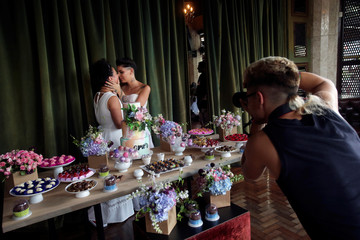 """Newlywed Alesandra Rufino and Moyra Madeira kiss as they pose for a picture after a collective wedding ceremony for 38 same-sex couples organized by """"House 1"""", an NGO and residential shelter in Sao Paulo"""