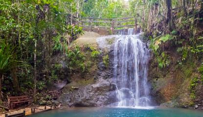 A bench at the end of hiking trail to enjoy a waterfall in Colo-i-Suva rain forest national park, nature reserve near Suva, Viti Levu island, Fiji, Melanesia, Oceania.