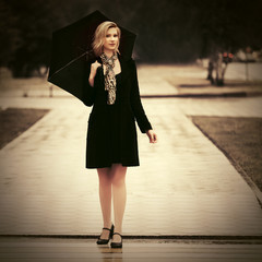 Happy young fashion woman with umbrella walking on city street