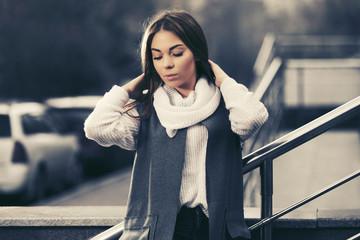 Sad young fashion woman in gray sleeveless coat walking on city street