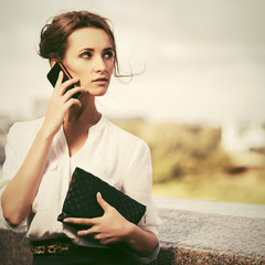 Young fashion business woman with handbag calling on cell phone on city street