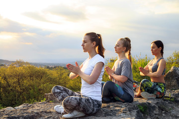 Young woman practicing yoga or pilates at sunset or sunrise in beautiful mountain location.